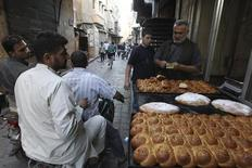 A street vendor sells traditional bread before the time for iftar, or breaking fast, during the Muslim fasting month of Ramadan in Aleppo, July 16, 2013. Picture taken July 16, 2013. REUTERS/Muzaffar Salman