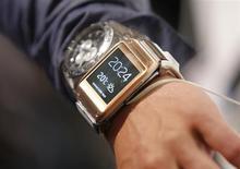 """Журналист примеряет часы Galaxy Gear на выставке IFA в Берлине 4 сентября 2013 года. Samsung Electronics Co Ltd и Qualcomm Inc представили """"умные часы"""", штурмуя рынок """"нательных"""" гаджетов потенциальным объемом $50 миллиардов на фоне постепенного замедления продаж смартфонов. REUTERS/Fabrizio Bensch"""