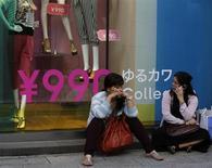 Женщины сидят у магазина одежды в Токио 27 июня 2013 года. Управляющий Банка Японии Харухико Курода сообщил, что центробанк готов предпринять дальнейшие шаги по смягчению денежно-кредитной политики в случае, если налог с продаж или другие риски помешают достижению инфляционного ориентира на уровне 2 процентов. REUTERS/Toru Hanai