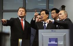 Премьер-министр РФ Владимир Путин (справа) и глава Газпрома Алексей Миллер (слева) показывают председателю КНР Ху Цзиньтао (в центре) диспетчерскую в центральном офисе Газпрома в Москве 16 июня 2011 года. Российский газоэкспортный монополист Газпром и китайская госкомпания CNPC подписали основные условия контракта по поставке в КНР российского газа по восточному маршруту, сказал глава Газпрома Алексей Миллер. REUTERS/Alexander Nemenov/Pool
