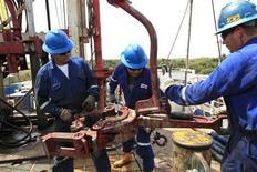 Empleados de la compañía petrolera canadiense Pacific Rubiales trabajan junto a tubos de perforación en el Campo Rubiales en Meta, al este de Colombia. 23 de enero, 2013. REUTERS/Jose Miguel Gomez (COLOMBIA - ENERGIA NEGOCIOS)