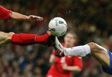 Игроки сборных Уэльса Саймон Дэвис (слева) и Азербайджана Аслан Керимов борются за мяч в матче отборочного турнира ЧМ-2006 в Кардиффе 12 октября 2005 года. REUTERS/Ian Hodgson