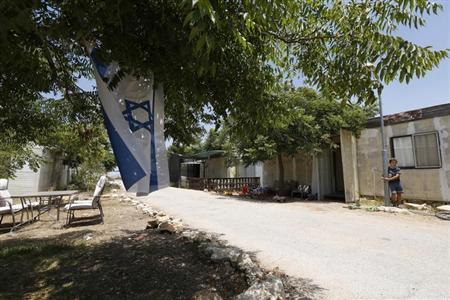 A boy stands near an Israeli flag in the West Bank Jewish settlement of Ofra, north of Ramallah July 18, 2013. REUTERS/Baz Ratner