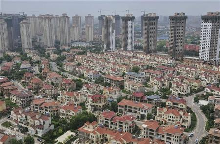 A block of villa residences is seen in front of new residential buildings under construction in Shenyang, Liaoning province July 18, 2013. REUTERS/Stringer