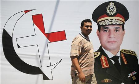 An anti-Mursi supporter of Egypt's army walks in front of his shop, with huge posters of Egypt's army chief General Abdel Fattah al-Sisi with cross and crescent symbol of the unity of Egyptians in downtown Cairo August 7, 2013. REUTERS/Amr Abdallah Dalsh