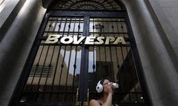 Mulher bebe café em frente à bolsa de valores BM&FBovespa em São Paulo. O principal índice da Bovespa teve sua quarta sessão consecutiva de ganhos nesta segunda-feira, na medida em que dados fortes da China ofuscaram a cautela de investidores ante a perspectiva de redução de estímulos do banco central norte-americano. 18/02/2011 REUTERS/Nacho Doce