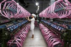 An employee works inside a silk factory in Neijiang, Sichuan province, in this July 3, 2013 file photo. China's factory output grew at its fastest pace in 17 months and investment and consumption beat market forecasts, increasing confidence among investors that the world's second-largest economy has halted a slide and is building some momentum. REUTERS/China Daily/Files