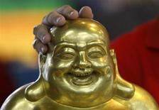 Статуя Будды из золота и фарфора в магазине в Сингапуре 30 августа 2013 года. Цены на золото снижаются на фоне спада на рынке нефти и укрепления фондовых рынков. REUTERS/Edgar Su