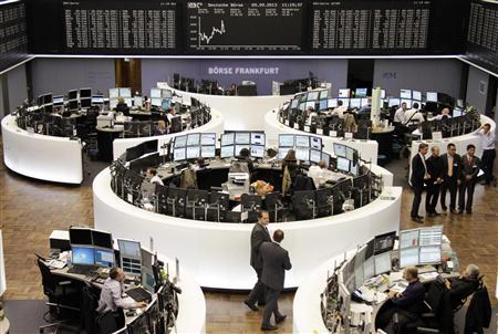 Traders are pictured at their desks in front of the German share price index DAX board at the Frankfurt stock exchange September 9, 2013. REUTERS/Remote/Pablo Sanchez