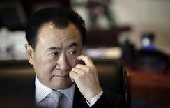 Wang Jianlin, chairman of Dalian Wanda Group, touches his face during an interview at his office in the company's headquarters in Beijing December 3, 2012. REUTERS/Suzie Wong