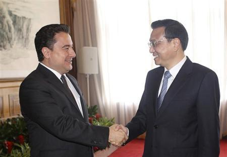 China's Premier Li Keqiang shakes hands with Turkey's Deputy Prime Minister Ali Babacan (L) during the Annual Meeting of the New Champions, also known as the ''Summer Davos'', in Dalian, Liaoning province, September 11, 2013. REUTERS/China Daily