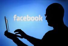Las acciones de Facebook Inc subieron el miércoles más de un 3 por ciento a un nuevo máximo, valorizando la primera red social del mundo en 106.000 millones de dólares, mientras los inversionistas se enfocaban en sus recientes avances en publicidad para móviles. En la foto de archivo, un hombre junto a una pantalla con el logo de Facebook en Bosnia. Ago 14, 2013. REUTERS/Dado Ruvic