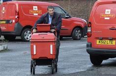Postier à Londres. Le gouvernement britannique a franchi jeudi une nouvelle étape dans la plus importante privatisation lancée depuis près de vingt ans en annonçant que la majorité du capital de Royal Mail serait cotée en Bourse dans les prochaines semaines. Le groupe britannique de services postaux devrait être valorisé de deux à trois à milliards de livres sterling (2,4 à 3,5 milliards d'euros). /Photo prise le 12 septembre 2013/REUTERS/Paul Hackett
