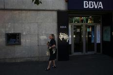 Un mujer pasea a su perro a las afueras de una sucursal del banco BBVA en Madrid, jul 31 2013. El banco español BBVA dijo que invertirá 2.500 millones de dólares en América del Sur hasta 2016 para aumentar su red de distribución y potenciar la banca online. REUTERS/Susana Vera