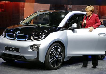 German Chancellor Angela Merkel opens the door of the new BMW i3 electric car during the official opening of the Frankfurt Motor Show (IAA) in Frankfurt September 12, 2013. REUTERS/Kai Pfaffenbach