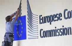 A worker adjusts and cleans the logo of the European Commission at the entrance of the Berlaymont building, the EC headquarters, in Brussels September 12, 2013. REUTERS/Yves Herman