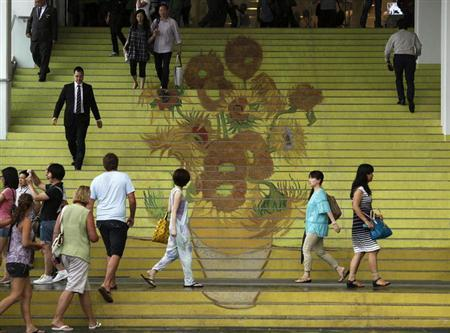 People walk on stairs featuring a five-metre-high reproduction of Vincent van Gogh's signature painting ''Sunflowers'', at the entrance to Ocean Terminal in Hong Kong July 15, 2013. A premium three-dimensional reproduction of works of van Gogh, the RELIEVO collection, approved by the curators of the Van Gogh Museum in Amsterdam, is on display at a gallery inside Harbour City shopping mall attached to the terminal. REUTERS/Bobby Yip