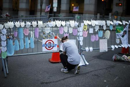 A woman kneels and cries in front of a memorial to the Boston Marathon bombings victims, at the barricades surrounding the scene in Boston, Massachusetts April 18, 2013. REUTERS/Brian Snyder