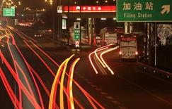 Cars drive into a Petrol China gas station, as other vehicles drive past on the Beijing-Tibet expressway in Beijing, March 23, 2012. CREUTERS/Soo Hoo Zheyang