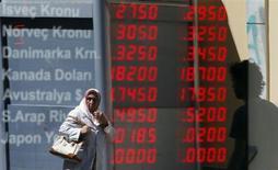Женщина на фоне вывески пункта обмена валют в центре Стамбула 21 июня 2013 года. Рубль вырос в начале торгов понедельника к бивалютной корзине и ее компонентам, продолжая отыгрывать мягкое разрешение ситуации вокруг Сирии и в ожидании итогов заседания ФРС в середине недели. REUTERS/Marko Djurica