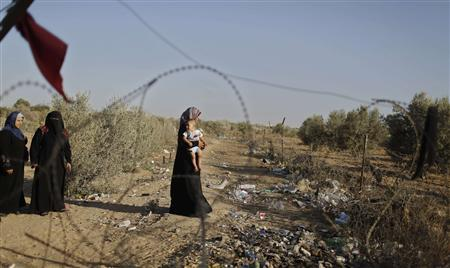 A Palestinian woman carries her son during a rally calling on Egyptian authorities to open the Rafah border crossing, outside the crossing in the southern Gaza Strip September 17, 2013. REUTERS/Mohammed Salem