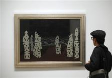 "A visitor looks at the painting ""The Finery of the Storm"" (1927) by artist Rene Magritte during the private opening of the exhibition ""Magritte: The Mystery of the Ordinary"" at The Museum of Modern Art in New York September 17, 2013. REUTERS/Joshua Lott"
