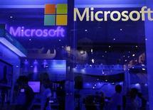 Люди на стенде Microsoft на выставке Computex в Тайбэе 4 июня 2013 года. Технологический гигант Microsoft Corp объявил в понедельник о повышении квартальных дивидендов на 22 процента и запуске программы выкупа акций размером $40 миллиардов накануне встречи с инвесторами, которые, как ожидается, раскритикуют уходящего главу компании из-за дорогостоящих вложений в рынок мобильных устройств. REUTERS/Pichi Chuang