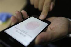 Un periodista probando el nuevo sistema de reconocimiento dactilar del teléfono iPhone 5s en Pekín, sep 11 2013. El lector por huella digital del iPhone 5S de Apple recibió buenas reseñas de dos influyentes críticos por su facilidad de uso, lo que ayuda a disipar las preocupaciones sobre la tecnología de escáner que ha generado poca fiabilidad en otros teléfonos móviles. REUTERS/Jason Lee