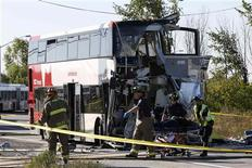 Emergency workers take a person away on a stretcher at the scene of an accident involving a bus and a train in Ottawa September 18, 2013. REUTERS/Chris Wattie