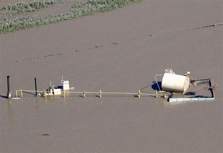 An oil storage tank on a well pad lies toppled by flood waters in Weld County, Colorado September 17, 2013. REUTERS/Rick Wilking