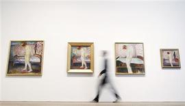"""Duncan Holden of the Tate poses with four paintings of Edvard Munch's """"Weeping Woman"""" series at the Tate Modern in London's Southbank, June 26, 2012. REUTERS/Andrew Winning"""