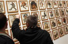 Visitors view a wall of Saturday Evening Post magazine covers featuring the art of Norman Rockwell at the Dulwich Picture Gallery in London in this file photo taken January 15, 2011. REUTERS/Chris Helgren/Files
