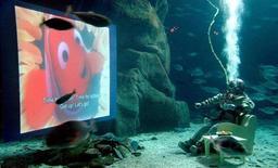 """Британец Ллойд Скотт смотрит мультфильм """"В поисках Немо"""" в Лондонском аквариуме 22 февраля 2004 года. Акции Walt Disney Co упали на два процента после того, как компания сообщила, что откладывает выпуск сразу двух анимационных фильмов, над которыми работает ее студия Pixar: сиквела """"В поисках Немо"""" и """"Добропорядочного динозавра"""". REUTERS/David Bebber"""