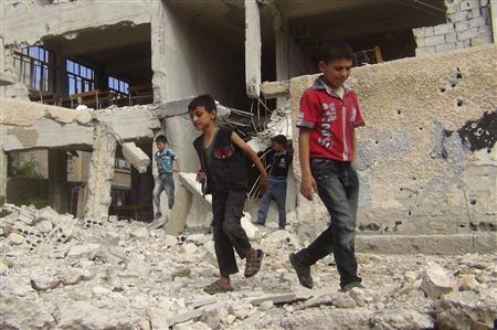 Children walk among debris from a damaged school building in the Damascus suburb of Zamalka September 19, 2013. Picture taken September 19, 2013. REUTERS-Abou Nidal alshami