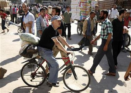 A man rides on a bicycle as people walk at the Karaj al-Hajez crossing, a passageway separating Aleppo's Bustan al-Qasr, which is under the rebels' control, and Al-Masharqa neighbourhoods, an area controlled by the regime, September 20, 2013. REUTERS-Ammar Abdullah