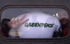 Активисты Greenpeace в автозаке в Москве 16 апреля 2002 года. Российские власти в пятницу задержали корабль Greenpeace и сообщили, что его экипаж может быть обвинен в пиратстве из-за протеста, во время которого экологи забрались на принадлежащую Газпрому буровую платформу в Арктике. REUTERS/Sergei Karpukhin