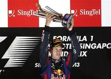 Red Bull Formula One driver Sebastian Vettel of Germany celebrates with the trophy after winning the Singapore F1 Grand Prix at the Marina Bay street circuit in Singapore September 22, 2013. REUTERS/Edgar Su