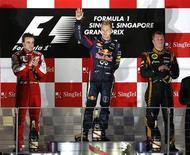 Piloto de Fórmula 1 da Red Bull, Sebastian Vettel (C), acena após vencer o GP de Cingapura. Vettel conquistou sem dificuldades sua terceira vitória no Grande Prêmio de Cingapura neste domingo e acumulou 60 pontos à frente de Fernando Alonso, da Ferrari, após dominar a corrida sob os holofotes do Circuito de Marina Bay Street. 22/09/2013 REUTERS/Edgar Su