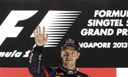 Red Bull Formula One driver Sebastian Vettel of Germany waves on the podium after the Singapore F1 Grand Prix at the Marina Bay street circuit in Singapore September 22, 2013. REUTERS/Pablo Sanchez