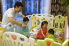 Tony Jiang poses with his three children at his house in Shanghai September 16, 2013. In December 2010, REUTERS/Aly Song
