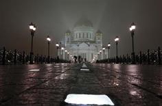 Люди проходят по мосту на фоне Храма Христа Спасителя в Москве 15 ноября 2009 года. Рабочая неделя в Москве будет холодной и дождливой, ожидают синоптики. REUTERS/Denis Sinyakov
