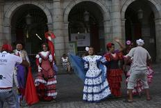 Tourists have their photo taken as they pose with flamenco dresses next to a sign that shows Madrid's 2020 Olympics candidate city logo at Madrid's Plaza Mayor square September 4, 2013. REUTERS/Susana Vera