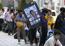 Люди в очереди за новым iPhone в Токио 20 сентября 2013 года. Apple Inc сообщила в понедельник о продаже 9 миллионов новых моделей смартфонов iPhone - 5s и 5c - за первые три дня после начала их продаж в пятницу. REUTERS/Toru Hanai