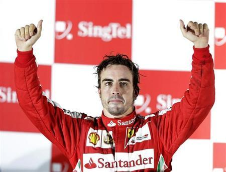 Ferrari Formula One driver Fernando Alonso of Spain gestures on the podium after the Singapore F1 Grand Prix at the Marina Bay street circuit in Singapore September 22, 2013. REUTERS/Pablo Sanchez