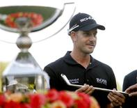 Henrik Stenson of Sweden accepts a replica of a Bobby Jones putter as he stands beside the FedExCup trophy after winning the the Tour Championship golf tournament at East Lake Golf Club in Atlanta, Georgia, September 22, 2013. REUTERS/Tami Chappell