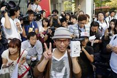 Homem posa para foto com caixa do iPhone 5s, da Apple, após ter esperado por dez dias na fila em frente à loja da Apple no distrito de Ginza, em Tóquio. A Apple anunciou nesta segunda-feira que vendeu 9 milhões de unidades dos novos modelos do iPhone, 5S e 5C, nos primeiros três dias após o lançamento dos aparelhos. As ações da empresa avançaram após o anúncio. 20/09/2013. REUTERS/Toru Hanai