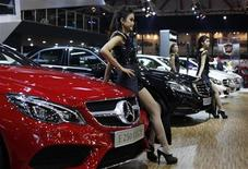Models stand beside the Mercedes E250 Coupe during the 21st Indonesia International Motor Show (IIMS) in Jakarta, September 23, 2013. REUTERS/Beawiharta