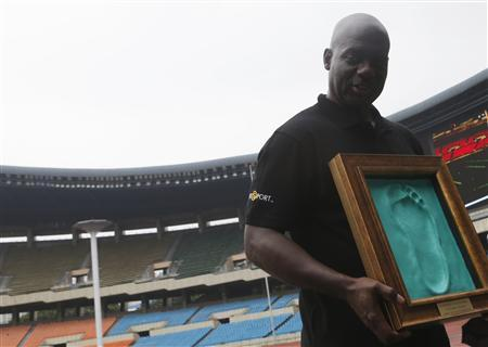 Sprinter Ben Johnson of Canada holds a cast of his footprint made after running on the track at the Seoul Olympic Stadium in Seoul September 24, 2013. REUTERS/Lee Jae-Won
