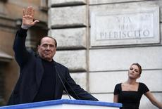 Former Italian Prime Minister Silvio Berlusconi waves to supporters as his girlfriend Francesca Pascale looks on during a rally to protest his tax fraud conviction, outside his palace in central Rome August 4, 2013. REUTERS/Alessandro Bianchi