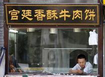 Un hombre utiliza un teléfono inteligente en un puesto de comidas en Pekín, sep 5 2013. El mayor mercado mundial de teléfonos inteligentes, China, probablemente verá envíos de más de 450 millones de dispositivos en 2014, al menos una cuarta parte más que este año, dijo la firma de análisis IDC. REUTERS/Kim Kyung-Hoon